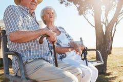 Couples supérieurs se reposant sur un banc avec le bâton de marche Photos stock