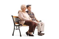 Couples supérieurs se reposant sur un banc et regardant loin Image stock