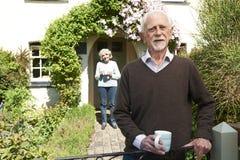 Couples supérieurs se tenant dans le jardin de cottage tenant la tasse de café Images libres de droits