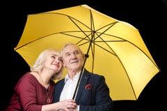 Couples supérieurs se tenant ensemble sous le parapluie jaune sur le noir Photos libres de droits
