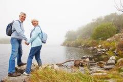 Couples supérieurs se tenant prêt un lac, souriant à un appareil-photo Image stock