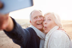Couples supérieurs se tenant sur la plage prenant Selfie Photos libres de droits