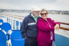 Couples supérieurs se tenant sur la plate-forme d'un bateau de croisière Photo libre de droits