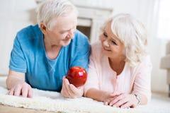 Couples supérieurs se trouvant sur le tapis avec la grande pomme rouge Photo libre de droits