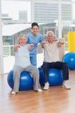 Couples supérieurs sur la boule d'exercis avec l'entraîneur Images stock