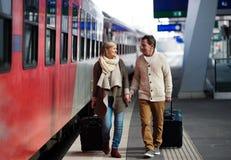Couples supérieurs sur la station de train tirant le bagage de chariot Photos libres de droits