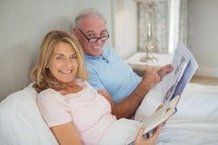 Couples supérieurs sur le journal et le livre de lecture de lit Photographie stock libre de droits