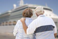 Couples supérieurs sur le rivage regardant le bateau de croisière Photos stock