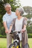 Couples supérieurs sur le tour de cycle au parc Image stock