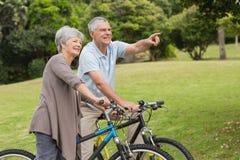 Couples supérieurs sur le tour de cycle dans la campagne Photos stock
