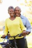 Couples supérieurs sur le tour de cycle dans la campagne Photo stock
