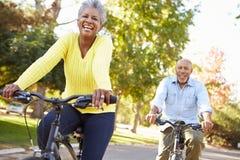 Couples supérieurs sur le tour de cycle dans la campagne Photo libre de droits