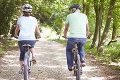 Couples supérieurs sur le tour de cycle dans la campagne Photographie stock libre de droits