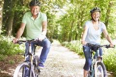 Couples supérieurs sur le tour de cycle dans la campagne Photos libres de droits