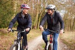 Couples supérieurs sur le tour de cycle dans la campagne d'hiver Photos stock