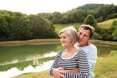 Couples supérieurs sur une promenade à étreindre de lac Photos stock