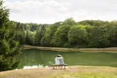 Couples supérieurs sur une promenade à étreindre de lac Image libre de droits