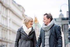 Couples supérieurs sur une promenade au centre de la ville L'hiver Photos libres de droits