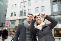 Couples supérieurs sur une promenade au centre de la ville prenant la photo Image libre de droits