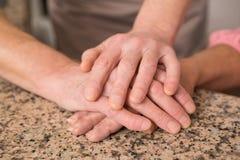 Couples supérieurs tenant des mains sur la table Images libres de droits
