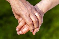 Couples supérieurs tenant des mains tout en se reposant ensemble dans le jardin Photographie stock