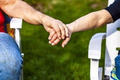 Couples supérieurs tenant des mains tout en se reposant ensemble dans le jardin Photo libre de droits