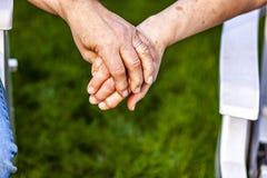 Couples supérieurs tenant des mains tout en se reposant ensemble dans le jardin Photographie stock libre de droits
