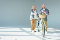 Couples supérieurs tenant la bicyclette proche Image stock