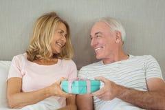 Couples supérieurs tenant le boîte-cadeau sur le lit Photos libres de droits
