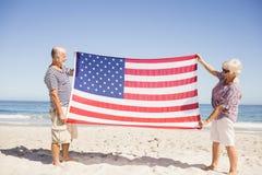 Couples supérieurs tenant le drapeau américain ensemble Photo libre de droits