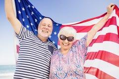 Couples supérieurs tenant le drapeau américain ensemble Photos stock
