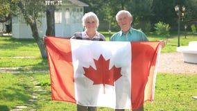 Couples supérieurs tenant le drapeau canadien banque de vidéos