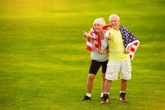 Couples supérieurs tenant le drapeau des Etats-Unis Images stock