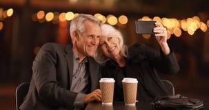 Couples supérieurs une date de soirée prenant des selfies avec le smartphone Photos stock