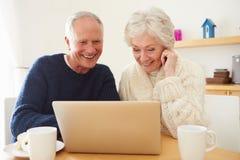 Couples supérieurs utilisant l'ordinateur portable à faire des emplettes en ligne Image stock
