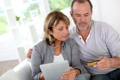 Couples supérieurs utilisant la carte de crédit faisant des emplettes en ligne Photographie stock
