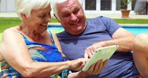 Couples supérieurs utilisant le comprimé numérique sur la chaise longue clips vidéos