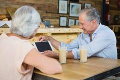 Couples supérieurs utilisant le comprimé numérique tout en ayant le café Images stock