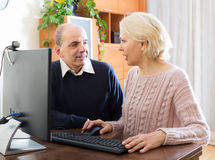 Couples supérieurs utilisant le PC à la maison Photos stock