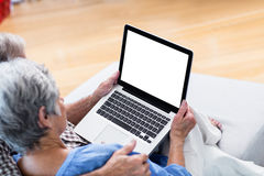 Couples supérieurs utilisant un comprimé numérique sur le sofa Photos libres de droits