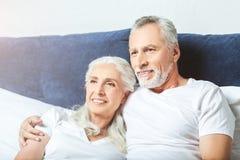 Couples supérieurs wathcing la TV à la maison images stock