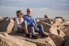 Couples sup?rieurs heureux se reposant sur des roches par la mer image libre de droits