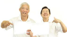 Couples supérieurs asiatiques heureux jugeant le signe vide blanc prêt pour pro Photo stock