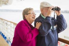 Couples supérieurs aventureux visitant le pays sur la plate-forme d'un bateau de croisière Photographie stock libre de droits
