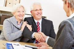 Couples supérieurs donnant la poignée de main Photographie stock