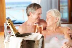 Couples supérieurs détendant à Bath buvant Champagne Together Images stock