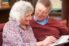Couples supérieurs faisant le jeu de mots croisé en journal ensemble Image libre de droits