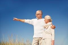 Couples supérieurs heureux indiquant le doigt quelque chose Image libre de droits