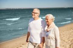 Couples supérieurs heureux marchant le long de la plage d'été Image libre de droits