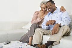Couples supérieurs heureux se reposant sur le sofa Images stock